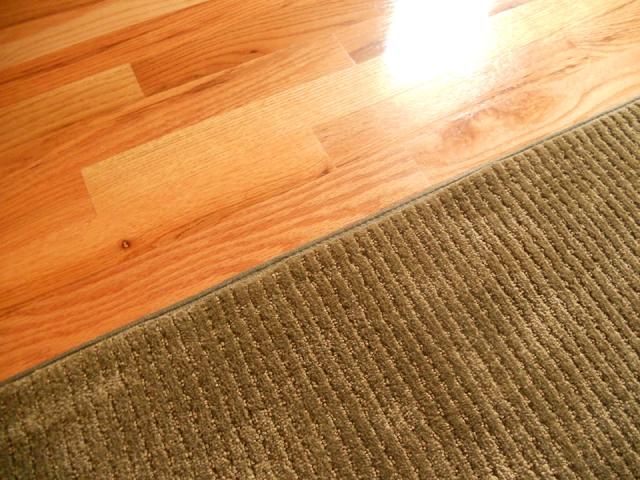 green rug on hardwood floor